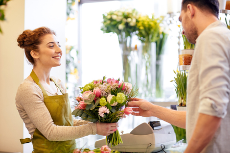 happy smiling florist woman making bouquet for and man or customer at flower shop