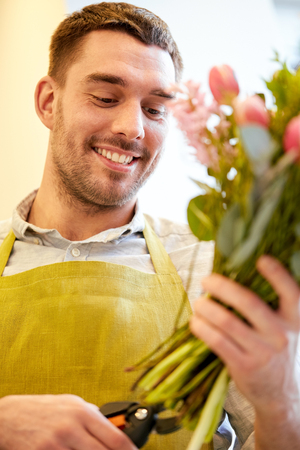 floristry: happy smiling florist man making bunch and cropping stems by scissors at flower shop