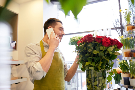florist man with red roses calling on smartphone at flower shop counter