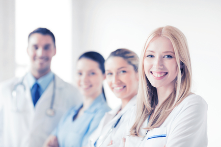 clinical staff: attractive female doctor in front of medical group Stock Photo