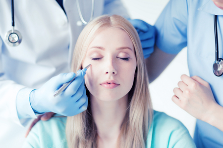 plastic surgeon: healthcare, medical and plastic surgery concept - plastic surgeon and nurse with patient in hospital