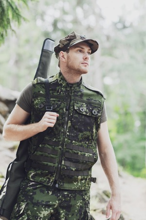 young soldier, ranger or hunter with gun walking in forest