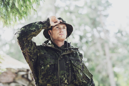 infantryman: young soldier or ranger wearing military uniform in forest