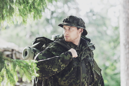 young soldier or ranger with backpack walking in forest Stock Photo