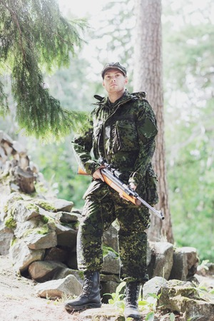 young soldier, ranger or hunter with gun in forest Stock Photo