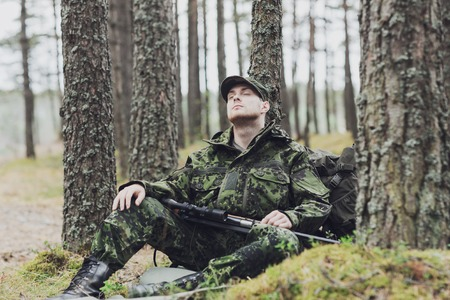 infantryman: young soldier, ranger or hunter with gun sitting and sleeping in forest Stock Photo