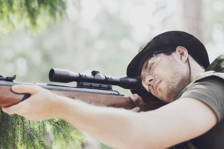 young soldier, ranger or hunter with gun aiming and shooting in forest
