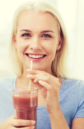 tomando jugo: sonriente jugo de consumición de la mujer o agitar a partir de vidrio en el hogar Foto de archivo