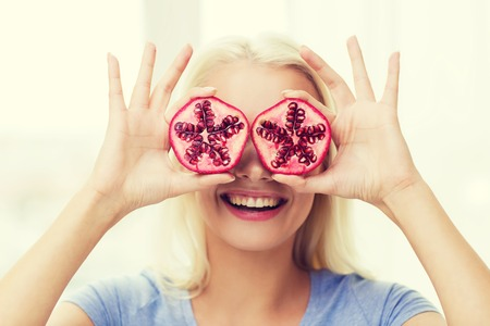 happy woman having fun and covering her eyes with pomegranate