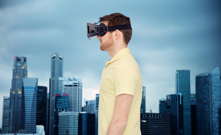 mediated: young man with virtual reality headset or 3d glasses over city skyscrapers background