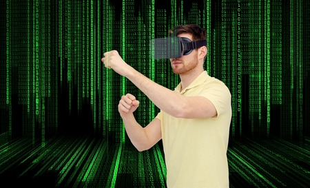 mediated: young man with virtual reality headset or 3d glasses playing game and fighting over binary code background