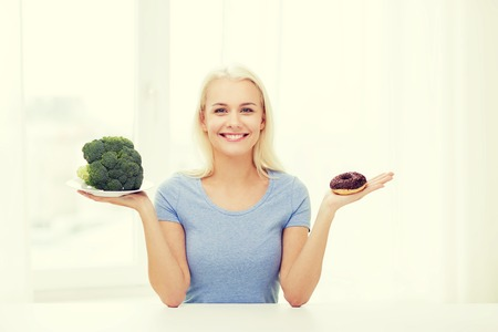 smiling woman choosing between broccoli and donut at home