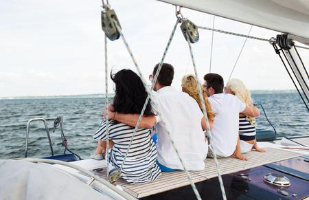 gelukkige vrienden zeilen en zittend op jacht of zeilboot dek