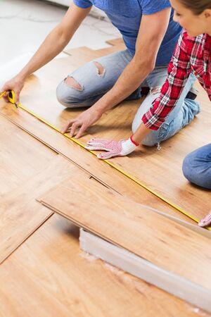 cinta metrica: Primer plano de pareja feliz con regla de medición tabla de parquet en casa