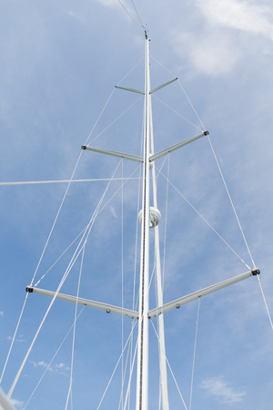 yachting: sailing, yachting and travel concept - close up of sailboat mast over blue sky