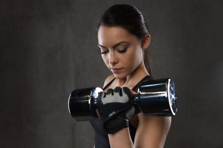 weightlifting gloves: young woman flexing muscles with dumbbells in gym