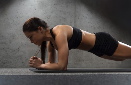 woman doing plank exercise on mat in gym Stockfoto