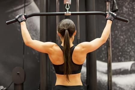 mujeres de espalda: Mujer que dobla los músculos en máquina de cable en el gimnasio Foto de archivo