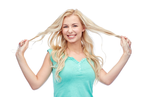 young woman smiling: smiling young woman or teenage girl holding strands of her hair