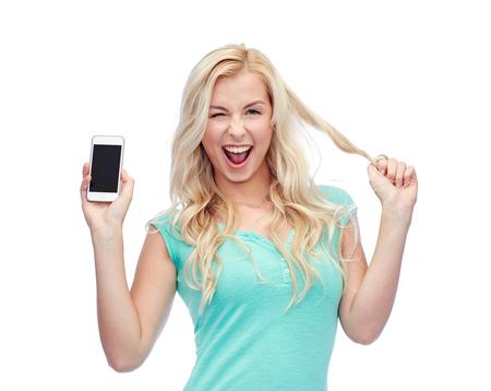 mujer alegre: sonriente mujer joven o adolescente que muestra la pantalla del teléfono inteligente en blanco y guiñando Foto de archivo