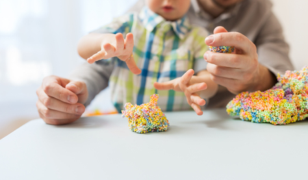 close up of happy father and little son playing with ball clay at home