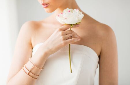bride bangle: glamour, beauty, jewelry and luxury concept - close up of beautiful woman with golden ring and bracelet holding flower