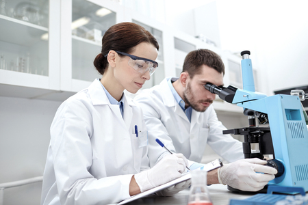 clinical laboratory: young scientists shaking glass with reagent and making test or research in clinical laboratory