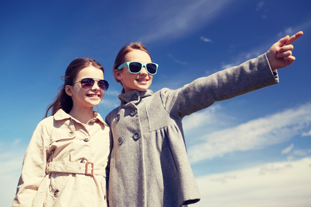 happy little girls in sunglasses hugging and pointing finger outdoors Stock Photo