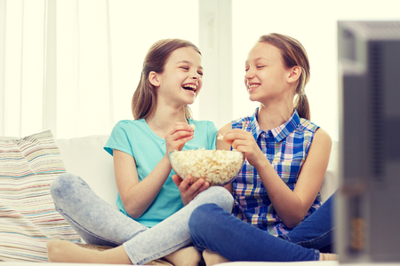 friends having fun: two happy little girls watching tv, laughing and eating popcorn at home Stock Photo