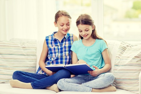 offsprings: two happy girls sitting on sofa and reading book at home Stock Photo