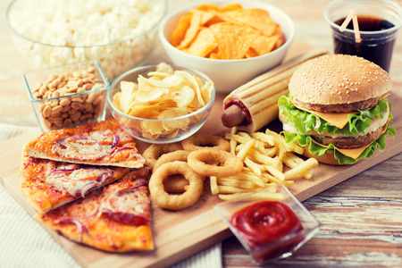 close up of fast food snacks and cola drink on wooden table Stock Photo