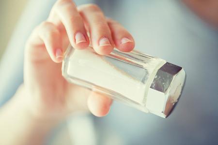 sal: Cerca de la mano que sostiene salero blanco