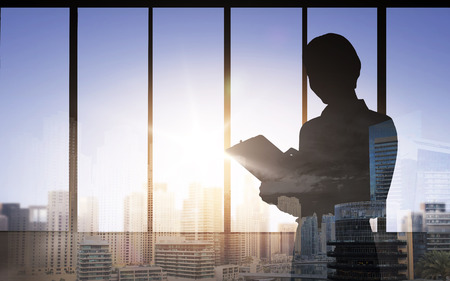 woman sunset: silhouette of woman with clipboard over double exposure office and city background