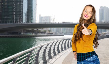 posing  agree: people, gesture, travel, tourism and fashion concept - happy young woman or teen girl in casual clothes showing thumbs up over dubai city street background