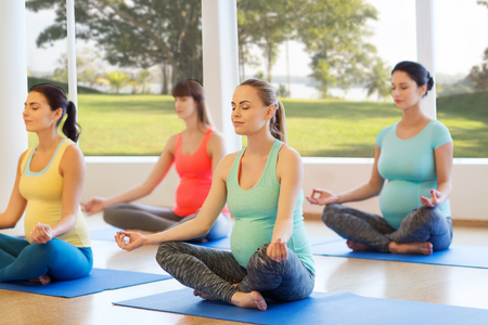 pregnancy, sport, fitness, people and healthy lifestyle concept - group of happy pregnant women exercising yoga and meditating in lotus pose in gym