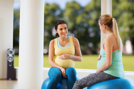 natural childbirth: pregnancy, sport, fitness, people and healthy lifestyle concept - two happy pregnant women sitting and talking on balls in gym over natural window view background Stock Photo