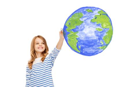 planeta tierra feliz: educación, escuela, día de la tierra y la gente feliz concepto - niña linda dibujo planeta tierra en el aire Foto de archivo