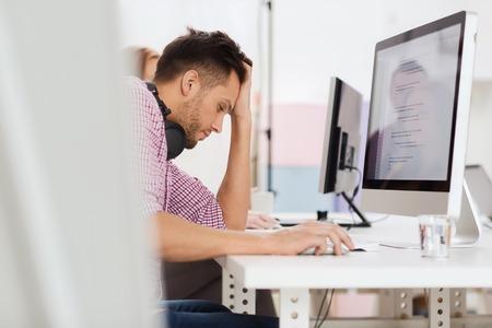 monitor de computadora: plazo, puesta en marcha, la educación, la tecnología y el concepto de la gente - triste desarrollador de software estresado o estudiante con los auriculares y la computadora en la oficina Foto de archivo