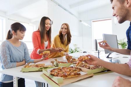 비즈니스, 음식, 점심 식사 및 사람들이 개념 - 행복 국제 비즈니스 팀 피자 사무실에서 먹고 스톡 콘텐츠