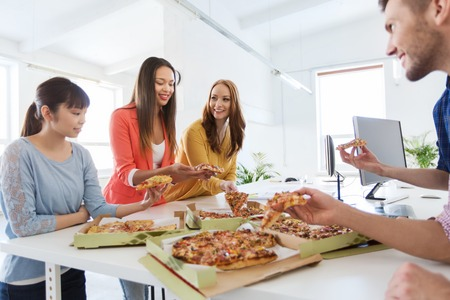 business, food, lunch and people concept - happy international business team eating pizza in office Stockfoto