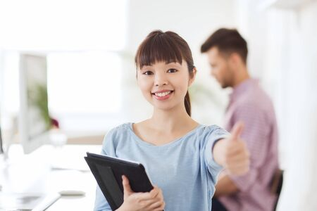 business, startup and people concept - happy asian businesswoman or creative female office worker with tablet pc computer showing thumbs up Stock Photo
