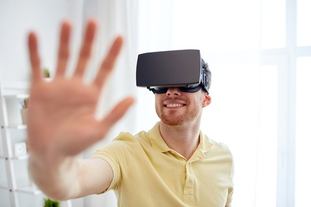 mediated: technology, gaming, entertainment and people concept - happy young man with virtual reality headset or 3d glasses playing video game Stock Photo