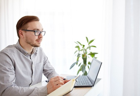 businessman thinking: business, startup, inspiration and people concept - happy businessman or creative male worker with notebook or diary thinking at home office