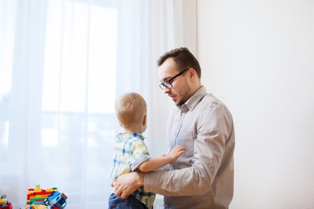 family, parenthood, fatherhood, care and people concept - father taking care of little son at home Stock Photo