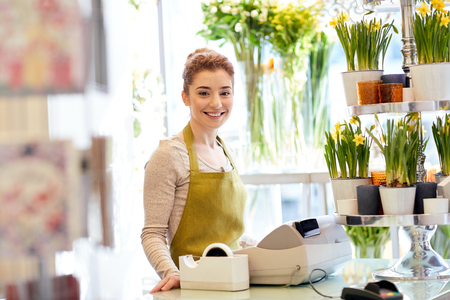 people, business, sale and floristry concept - happy smiling florist woman at flower shop cashbox Stock Photo