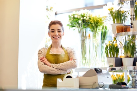 floristry: people, business, sale and floristry concept - happy smiling florist woman at flower shop cashbox Stock Photo