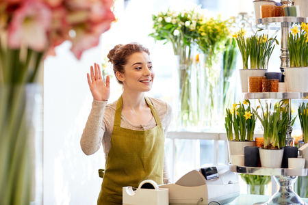 floristry: people, gesture, business, sale and floristry concept - happy smiling florist woman waving hand at flower shop cashbox Stock Photo