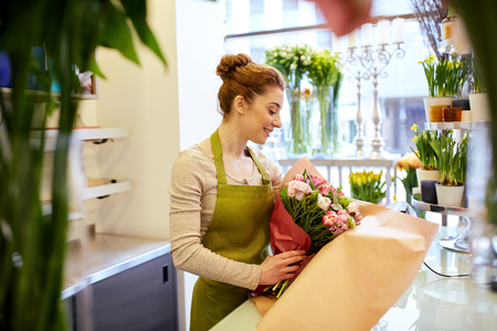 florist shop: people, business, sale and floristry concept - happy smiling florist woman wrapping bunch into paper at flower shop Stock Photo