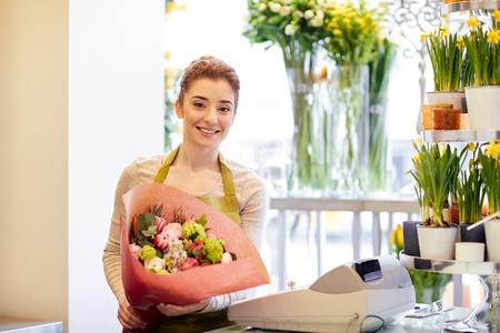 mensen, het bedrijfsleven, de verkoop en bloemisterij concept - gelukkig lachende bloemist vrouw met een bos bloemen verpakt in papier in bloemenwinkel Stockfoto