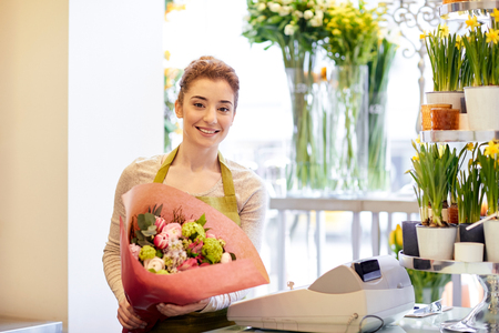 florist shop: people, business, sale and floristry concept - happy smiling florist woman holding bunch of flowers wrapped into paper at flower shop Stock Photo